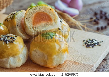 Delicious Chinese pastry or moon cake on wood cutting board with some ingredient on wooden table. Close up moon cake or Chinese pastry in side view. Homemade bakery concept of Chinese pastry for afternoon tea or coffee break.