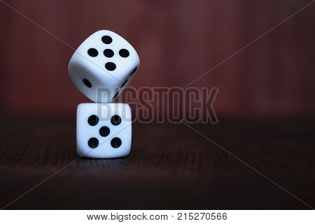 Pile of two white plastic dices on brown wooden board background. Six sides cube with black dots. Numbers 1 3 5.