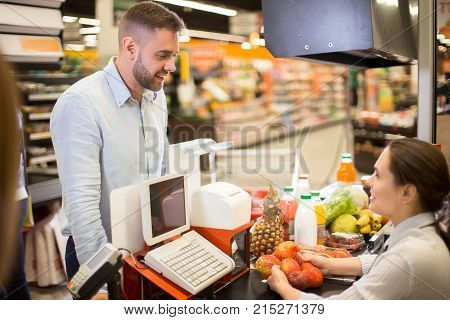 Portrait of handsome young man buying food in supermarket standing at cash desk smiling happily at cashier scanning prices