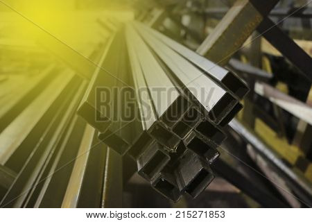 A Bundle Of Long Steel Square Tubes Of Black Metal With A Small Rust