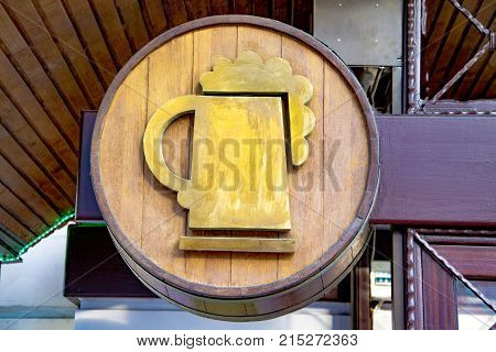 Beer barrel and beer glass is suspended over.