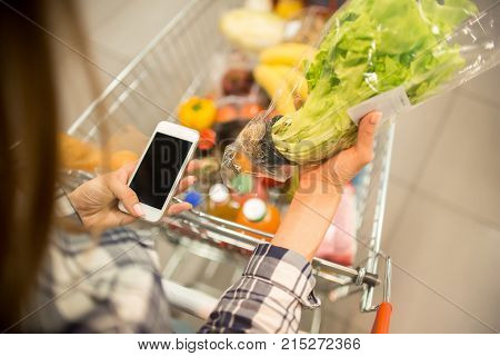 High angle of young woman buying groceries in supermarket pushing shopping cart and checking shopping list via smartphone