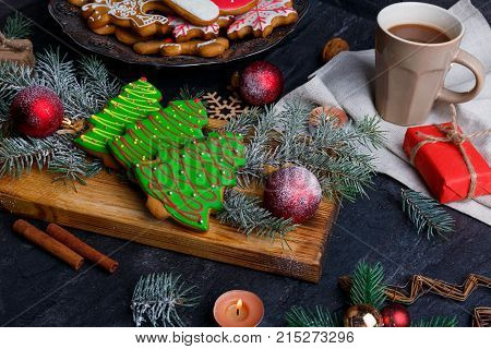 On the table a wooden board with Christmas cakes in the form of a Christmas tree, sprigs of a Christmas tree, a cup of tea and Christmas balls.