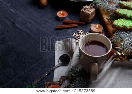 On a dark surface a cup of tea, a wooden board with sweet Christmas gingerbreads in the form of a Christmas tree, twigs of a Christmas tree and several burning small round candles. View from above.