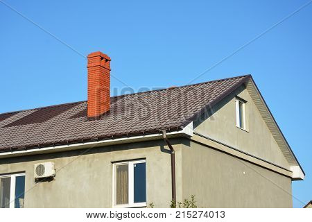 Repair replace metal roof with renovate and replace metal roof sheets. House with metal roof brick chimney rain gutter and insulate plaster wall outdoors.
