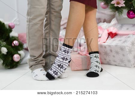 Two pairs of male and female legs in warm socks with patterns of penguins and snowflakes stand on a white carpet against the background of Christmas gift boxes. Female one leg on the male leg. Indoor.