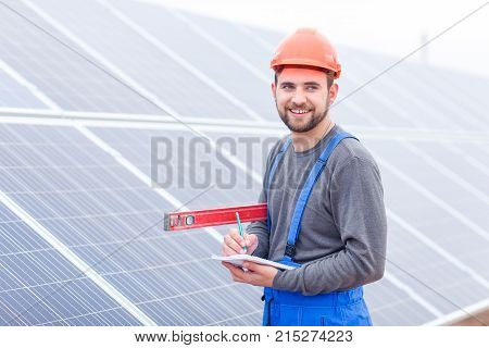 A smiling employee of a solar cell station in uniform and helmet stands with a waterpas in his hands and writes something into a notepad.