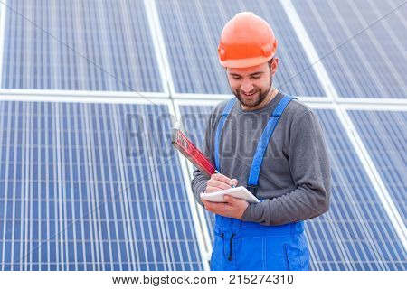 A bearded solar station worker in blue uniform and in an orange helmet, with a smile, writes something in a notebook holding waterpas in his hands.