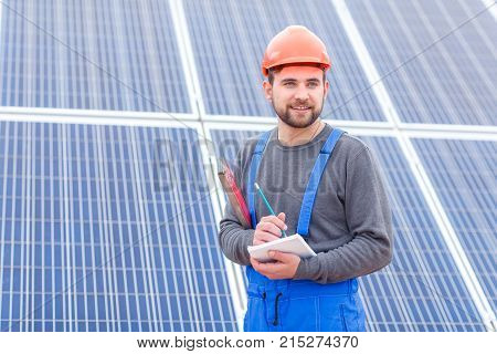 A young worker at a solar power station in blue uniform and in an orange helmet looks somewhere and writes something into a notebook holding waterpas in his hands.