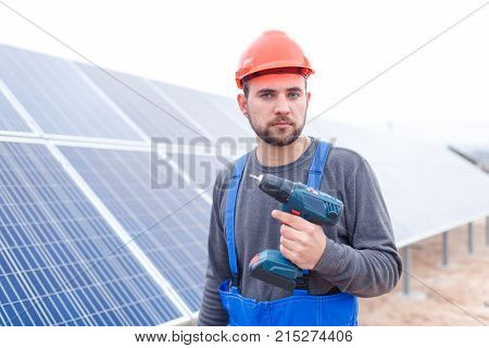 A serious employee of the solar cell station in a gray sweater, blue uniform and in an orange helmet, holds a drill in his hands.