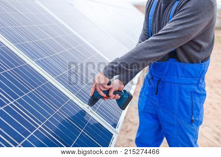 A solar station worker in blue uniform drills a solar battery panel. Outdoors.