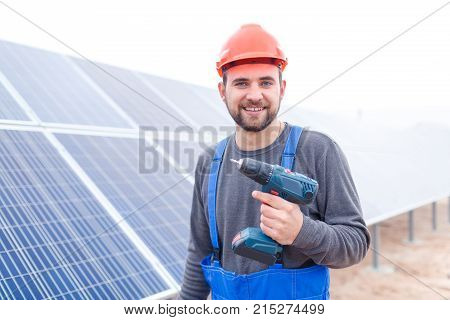 A man with a beard worker at a solar station in a blue uniform is smiling and holding a drill. Outdoors.