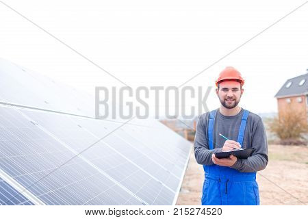 A solar station worker in blue uniform and an orange helmet stands near the solar battery panel smiling and writes something into a notepad. Outdoors.