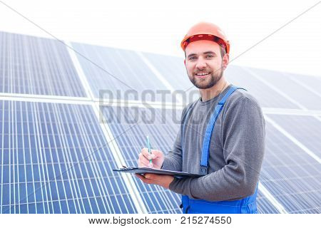 A solar station worker in uniform and a helmet stands on the background of a large panel of solar battery and records something in a notebook and smiles. Outdoors.