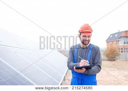 A happy worker stands at the solar station in uniform and helmet and writes something in a notebook with a smile. Outdoors.