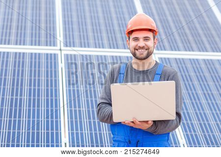 A happy worker at the solar battery station is dressed in a uniform and helmet and is holding a gray modern laptop. Outdoors.