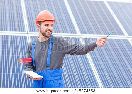 A young bearded worker at the solar battery station in blue uniform shows his hand somewhere and holds a notebook, a pencil and waterpas in his hands. Outdoors.