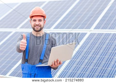 Experienced worker of the solar battery station in blue uniform and in an orange helmet holds a modern laptop in his hands and shows a thumbs-up gesture. Outdoors.