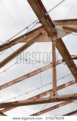 Trusses overhead and open to the sky with rust and strings of lights vertical aspect