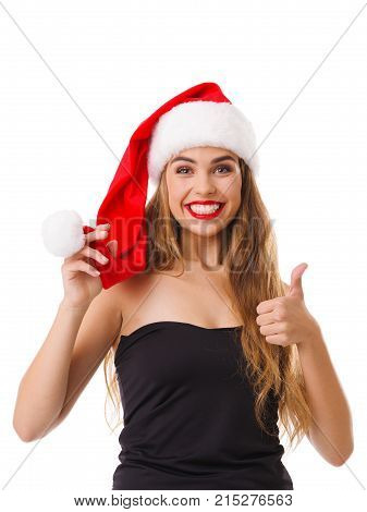 The happy girl in Santa's red hat smiles broadly and shows her thumb with one hand, and the second holds on to the pompon. Isolated on white background.