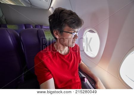 Man in red t-shirt sits in armchair in business class airplane salon looking into porthole.