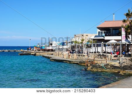 MELLIEHA, MALTA - APRIL 2, 2017 - Tourists relaxing at a pavement cafe in the harbour with boats in dry dock to the rear Mellieha Malta Europe, April 2, 2017.