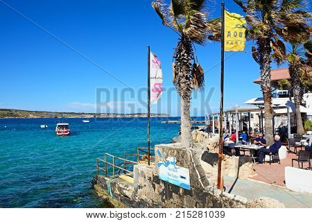 MELLIEHA, MALTA - APRIL 2, 2017 - Tourists relaxing at a pavement cafe with views across the bay Mellieha Malta Europe, April 2, 2017.