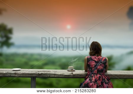Women check in. beautiful coffee shop in forest fog and wooden table misty mountain and sunset