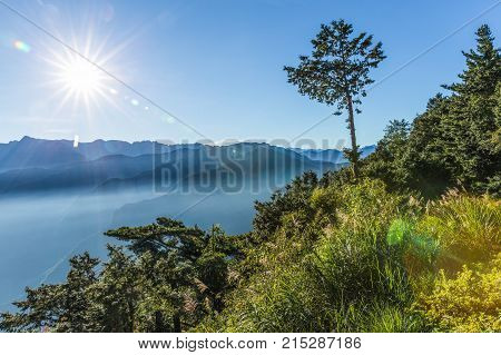 Morning view of shining sun on clear blue sky over complicated mountain range at Zhushan forest Alishan Recreation Area of Taiwan.