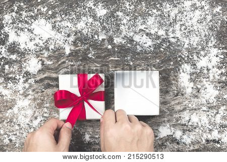 Man's Hand Wrapping Empty White Christmas Gift And Tying Bow With Red Ribbon On Old And Rustic Woode