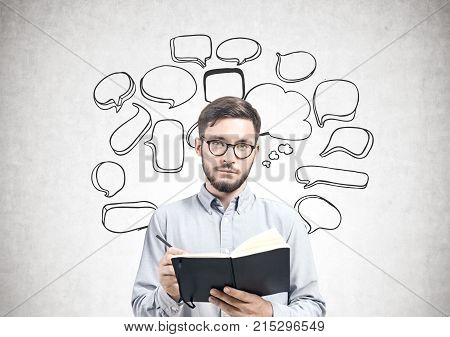 Portrait of a bearded young man wearing a blue shirt and glasses and holding an open planner and a pen. He is standing near a concrete wall with a speech bubbles sketch on it. Mock up