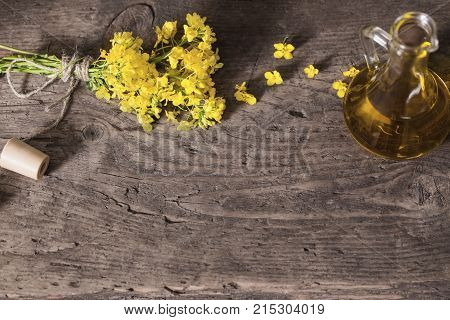 rapeseed oil (canola) and rape flowers on wooden table