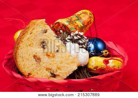 panettone, traditional italian Christmas cake of milan, with Christmas decoration on red backcloth