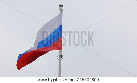 Russian flag on the flagpole waving in the wind against a blue sky with clouds.