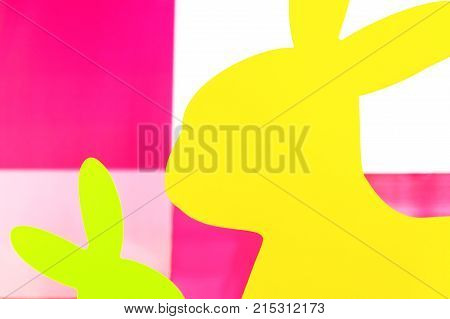 Happy Easter - parts of multicolored plastic rabbits against colorful background high contrast