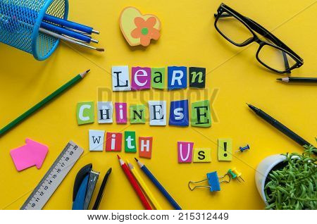Word LEARN CHINESE WITH US made with carved letters on yellow desk with office or school supplies, stationery. Concept of chinese language courses.