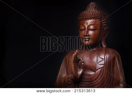 The pacified and obtained an enlightenment Buddha with the hand raised in gesture of vitarka mudra isolated on black background.