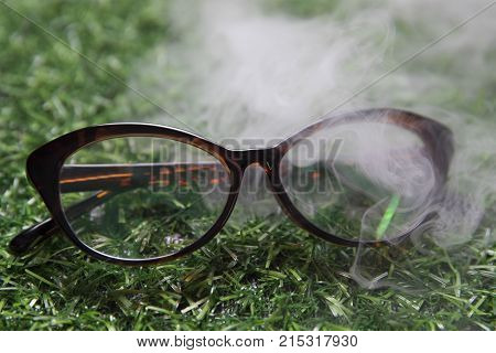 Eyeglass frames in smoke on a background of faux green grass
