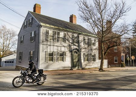 PORTSMOUTH, NH - FEBRUARY 28: Portsmouth, a city in Rockingham County, New Hampshire, is a popular summer destination. Old house with a motorbiker on the street on February 28, 2016