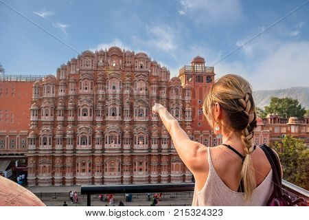 Beautiful young woman points to Hawa Mahal in Jaipur, Rajastan. Travel concept in India