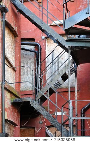 fire escape on an old abandoned housing development with derelict boarded up windows and red painted bricks