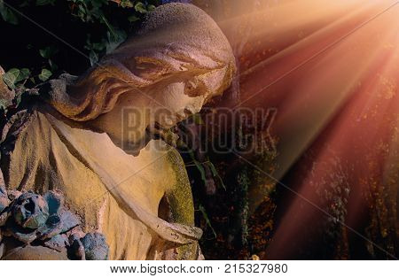 Ancient statue of wonderful angel in the rays of the sun (architecture archetype religion faith)