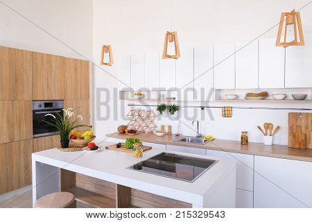 Kitchen design comfortable and functional, made in light colors in wood with oven and electric stove. In middle of room there bar table on which cutting board with vegetables, fruit in bowl with high chairs. In kitchen there regular and suspended boxes an
