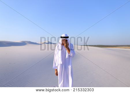 Cheerful Muslim guy walks along white sand of wide desert on warm summer evening. Arab young man in national clothes dances on spot and laughs giggly, adjusting hands with harness in wind. Swarthy, handsome Muslim with short dark hair dressed in kandura,