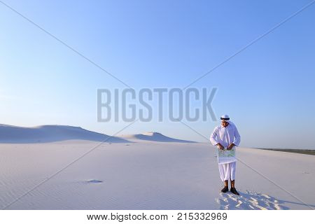 Successful Arab young male architect keeps in hands and looks at project drawing, finishes work, standing in middle of big desert outdoors on hot summer day. Swarthy Muslim with short dark hair dressed in kandura, long, spacious dress made of white unpain