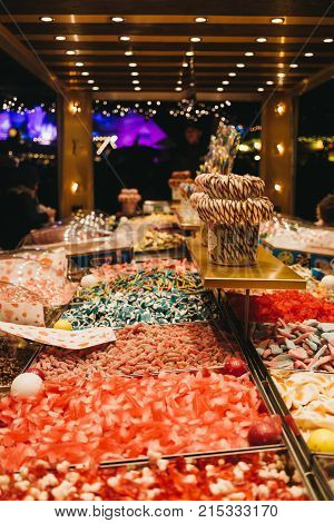 LONDON, UK - NOVEMBER 18, 2017: People purchase sweets at a pick'n'mix stall in Winter Wonderland, annual Christmas Fair in London, UK.
