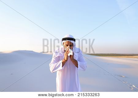 Sad handsome young man, sheikh ill with cold and feels unwell, eases breathing with handkerchief and looks to side, standing in middle of bottomless desert with snow-white sand on sunny summer day. Swarthy Muslim with short dark hair dressed in kandura, l
