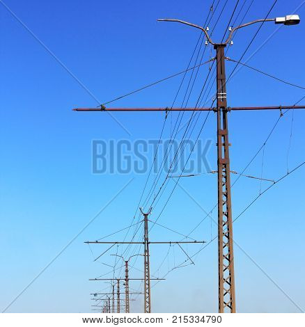 Railroad Railway Catenary Lines Against Clear Blue Sky.