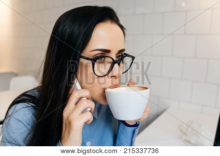 young business woman working at a cafe, talking on the phone about a business and drinking an invigorating coffee