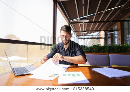 Placeman sorting papers on desk near laptop. Strong male hands with watch near window. Concept of stopping document clutter on workplace.
